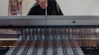 Person using a weaving machine